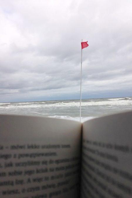 Czerwona flaga, fale, zimno i... ksiażka (widok z kosza plażowego)