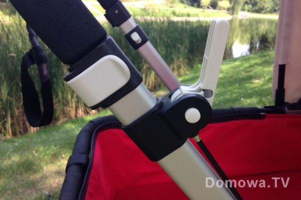 Od drugiej wersji regulacja rączki jest takimi zatrzaskami (białe elementy wózka sugerują, że coś da się zmienić/nacisnąć). W poprzedniej wersji były motylki. Hamulec jest ręczny – nie jest najwygodniejszy moim zdaniem, ale pod ręką