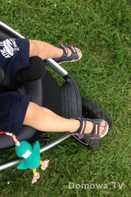 Nogi dwulatka w siedzisku spacerowym