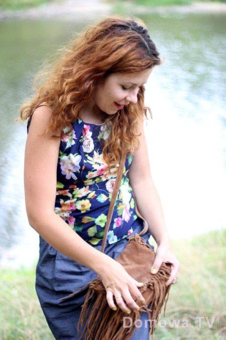 Bluzka w kwiaty, torebka z frędzlami, prosta spódnica