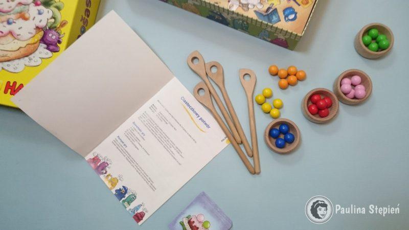Środek: pudło-miska, kulki, łyżki, miski i karty