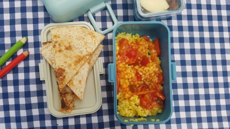 Pudełka dzieci, tutaj tortille oraz ryż z sosem slodko-kwaśnym