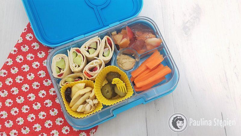 Tortille zawinięte z hummusem, ogórkiem i papryką, do tego suszone owoce, kiszony ogórek, galaretka i marchewki z hummusem