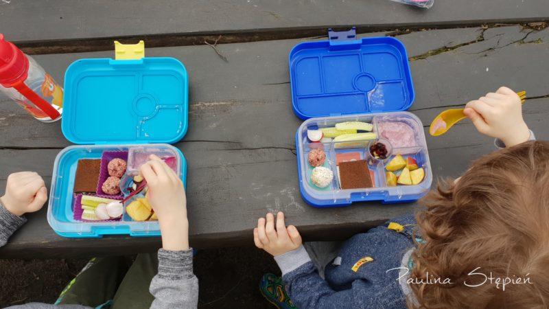 Chłopcy jedzą ze swoich pudełek